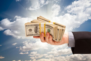 Male Hand Holding Stack of Cash Over Dramatic Clouds and Sky with Sun Rays