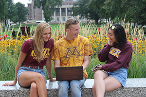 University of Minnesota students using a laptop outdoors