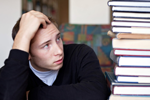stressed out student looks up at a high pile of textbooks