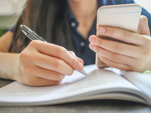 close up of student with textbook and cell phone