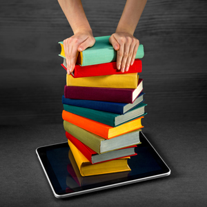 hands pushing stack of books into a tablet