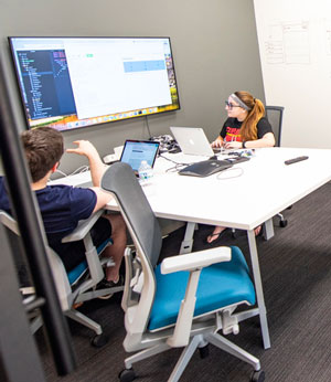Students participating in the code_orange program at Northern Illinois University present their work and ideas to peers and company representatives, providing them with an opportunity to experience Discover's company culture.