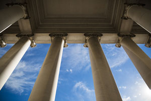view of blue sky through columns of a government building