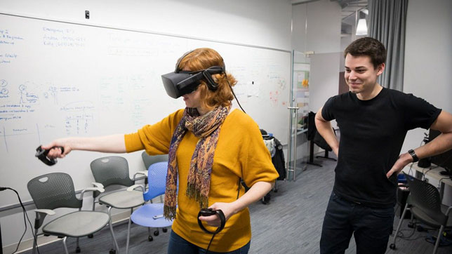 Jack Madden, a Cornell doctoral candidate in the field of astronomy, watches as Andrea Stevenson Won, assistant professor of communication and director of the university's Virtual Embodiment Lab, uses a virtual reality simulator.