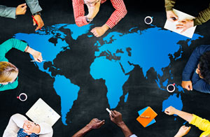 group of people sitting around map of globe