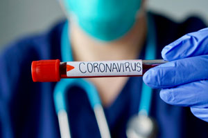 doctor holding up vial labeled coronavirus