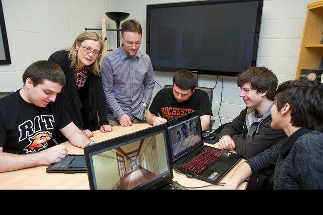 Rochester's Chair of Humanities, Lisa Hermsen, with Assistant Professor Shaun Foster and students view a virtual 3D model of the Buffalo State Asylum for the Insane. Photographer: A. Sue Weisler.