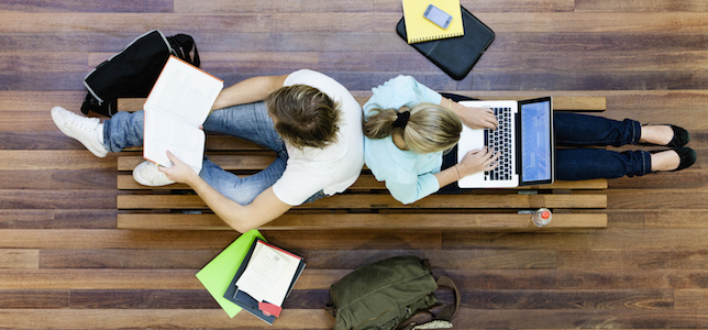 Overhead picture of students on a bench studying using technology
