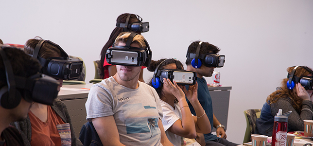 Students wear VR headsets to experience scenarios where cultural differences impact the way people communicate.