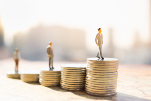 miniature people standing on stacks of coins