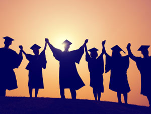 silhouette of college graduates with arms raised