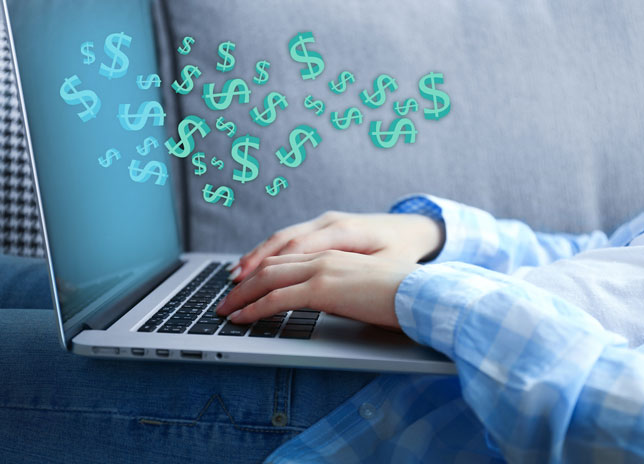 Woman using laptop with dollar bills coming out of the screen